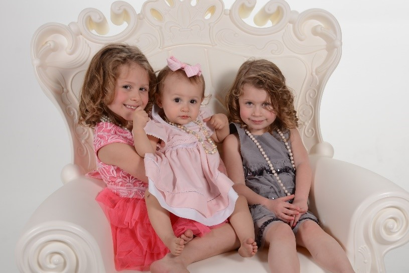 three young sisters smile for a professional portrait at andrae michaels portrait studios in colorado springs