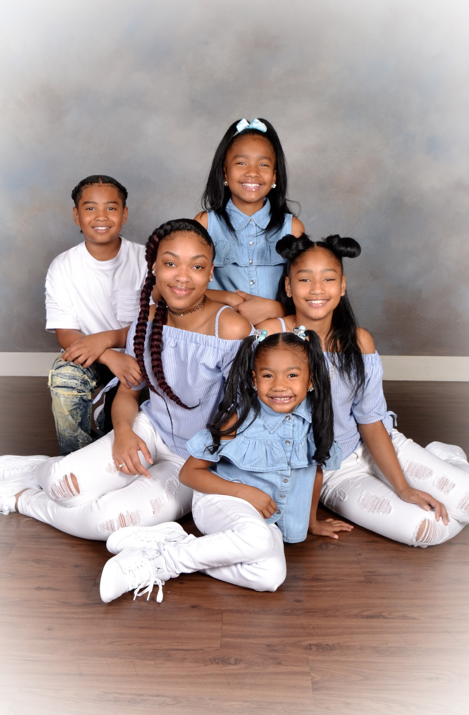 family with five siblings poses for professional studio portrait at andrae michaels portrait studios in colorado springs