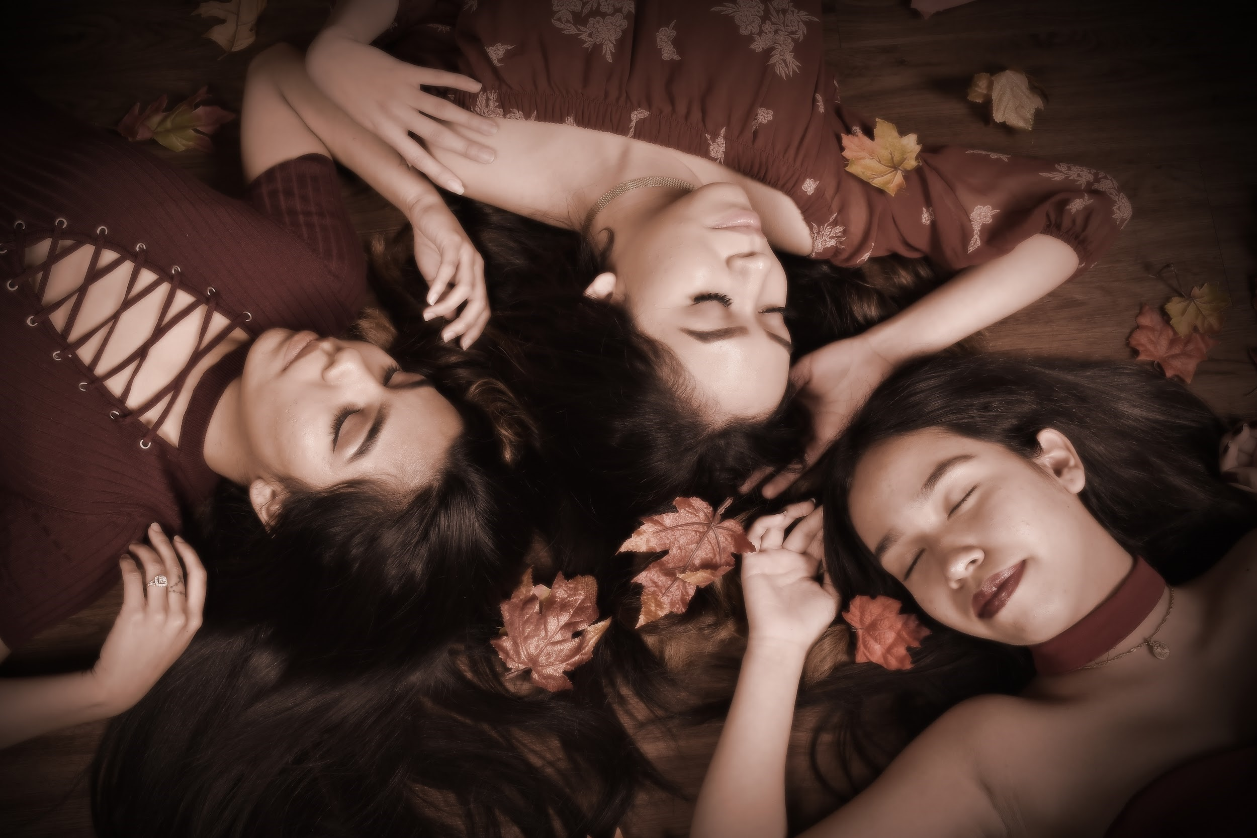 three young teenage sisters smile and pose for a professional portrait at andrae michaels portrait studios in colorado springs