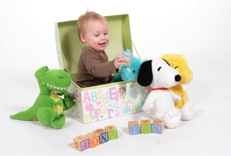 blond baby sitting in toy chest with stuffed animals by Andrea Michaels portrait studios