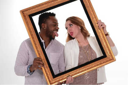 couple holds frame around them as they make silly faces at each other by Andrae Michaels portrait studios