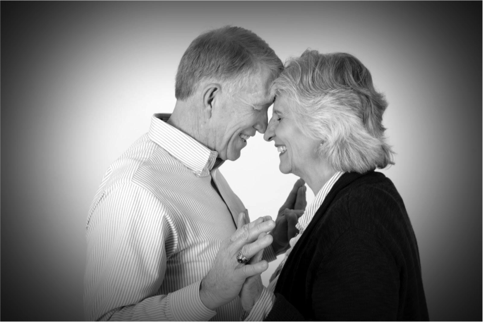 older couple smile at each other in black and white photograph by Andrea Michaels portrait studios