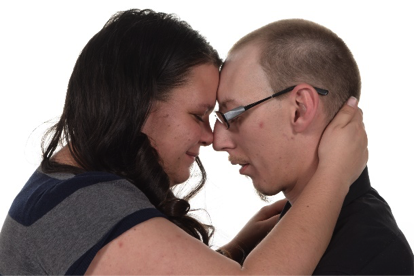 man and woman tilt their heads toward each other in romantic professional portrait by andrae Michaels portrait studios