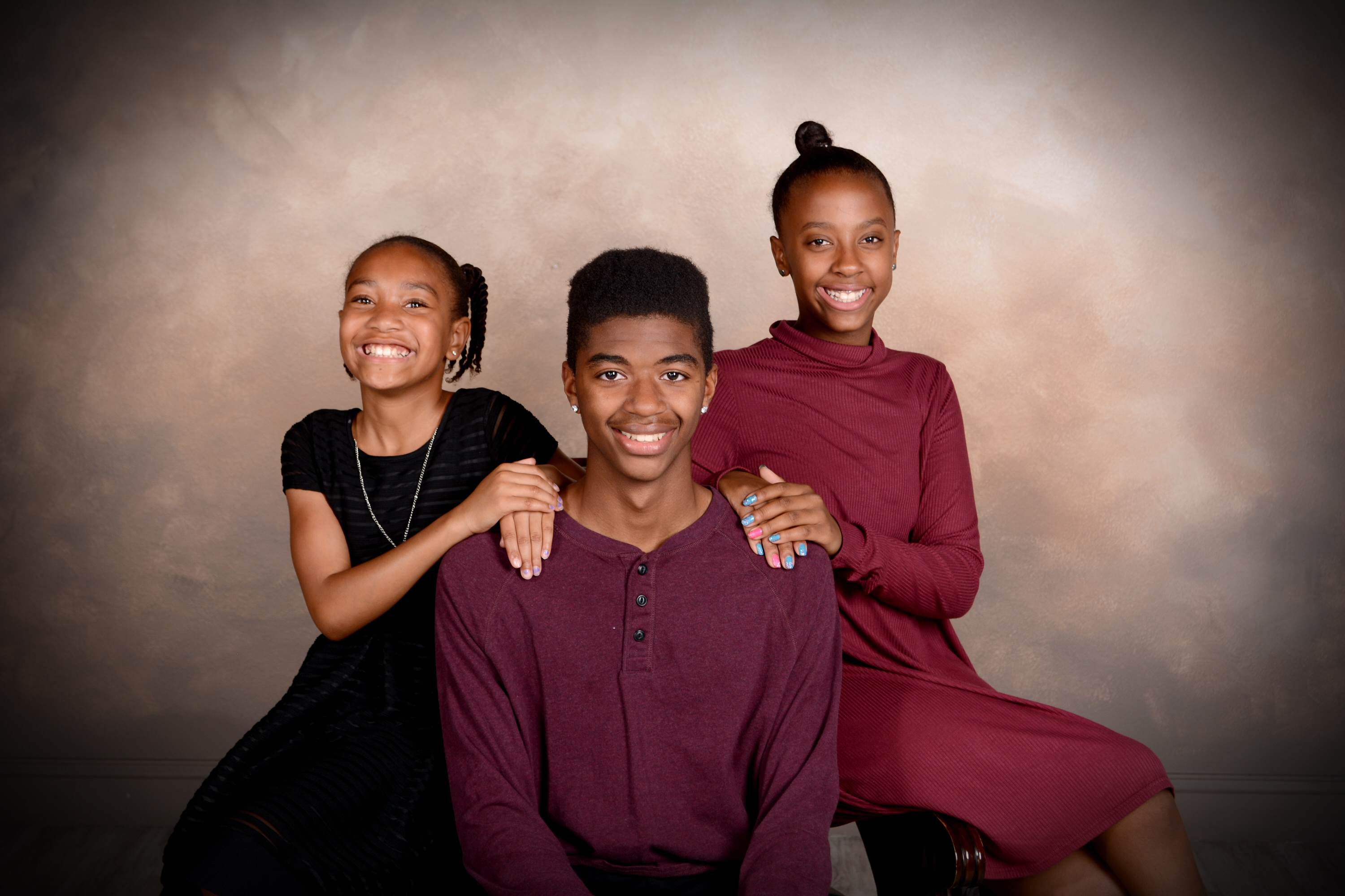 Andrae Michaels portrait studios captures three siblings smiling for the camera