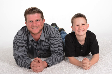 father and son smile for a professional studio portrait by Andrae michaels portrait studios
