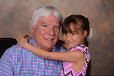 granddaughter and grandfather smile for professional portrait