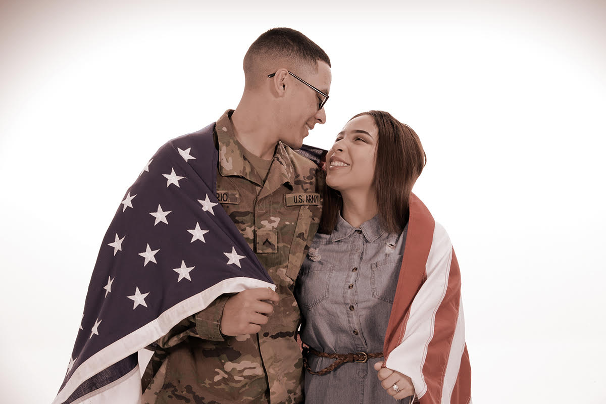 military couple with American flag wrapped around their shoulders captured at Andrea Michaels portrait studios