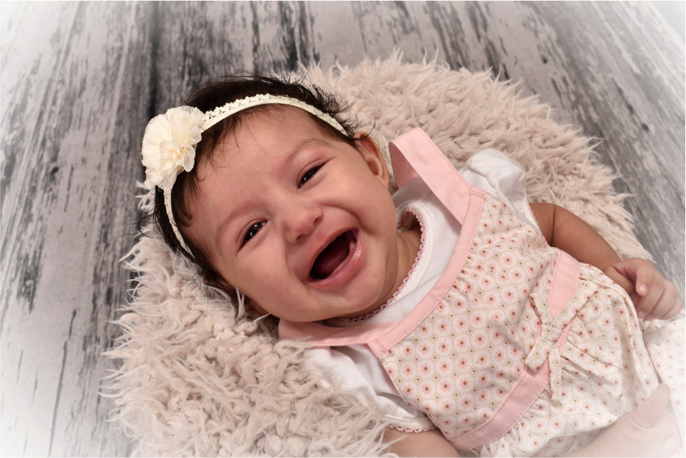 professional portrait of baby laughing for the camera by Andrae Michaels